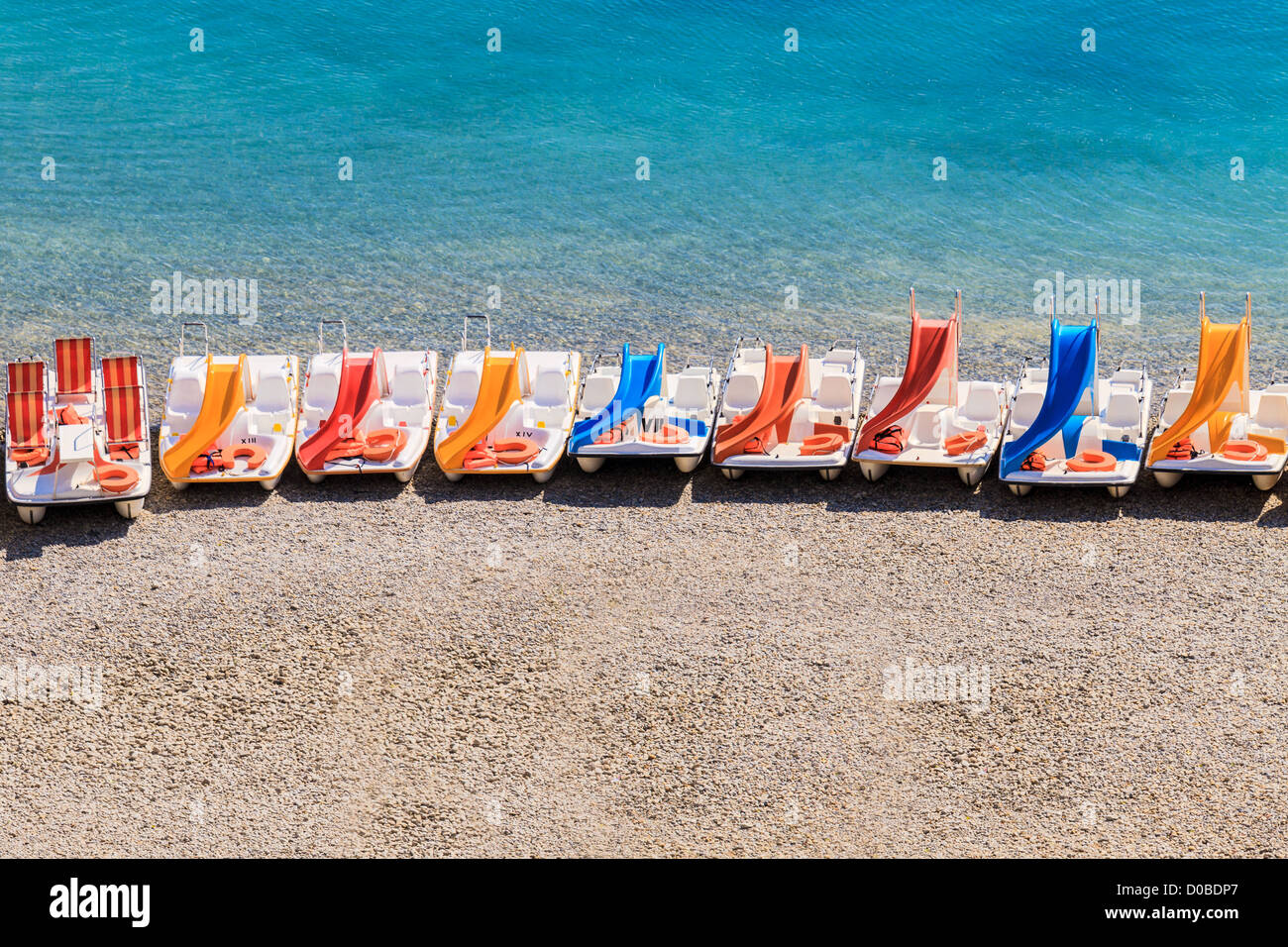 Colorful pedal boats on a stony beach - Stock Image