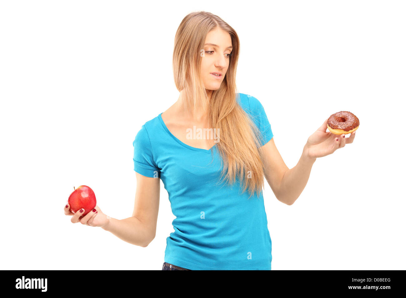 Doubtful woman holding an apple and donut trying to decide which one to eat - Stock Image