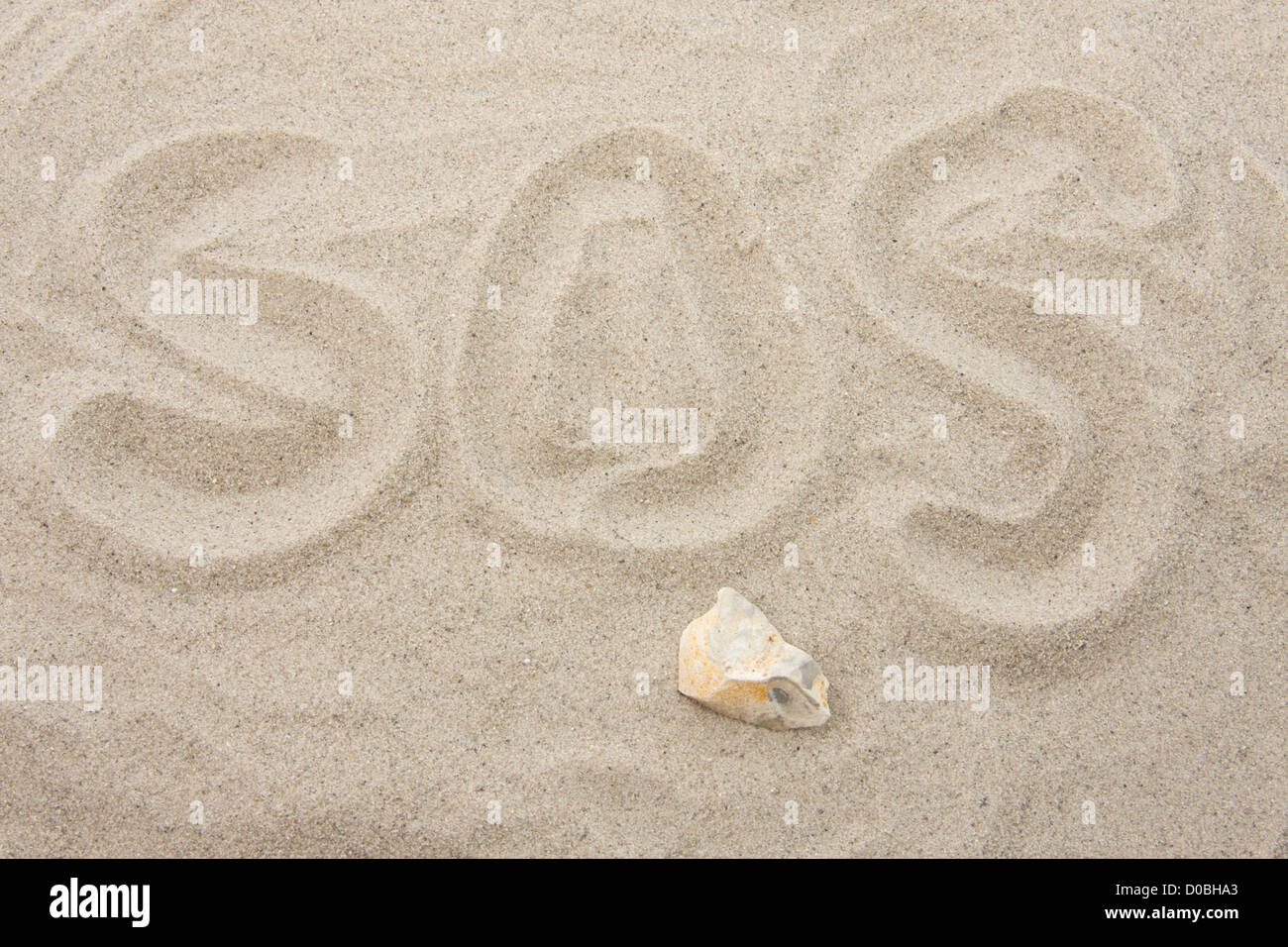 SOS letters written in sand - Stock Image