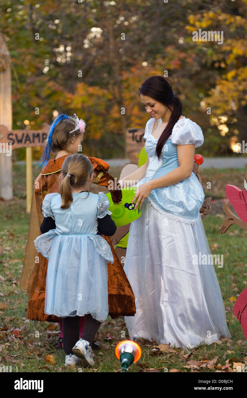 Teenage Girl in Princess Costume Giving Candy to Two Little Girls in Costume during Little Goblens Galore at Iroquois - Stock Image