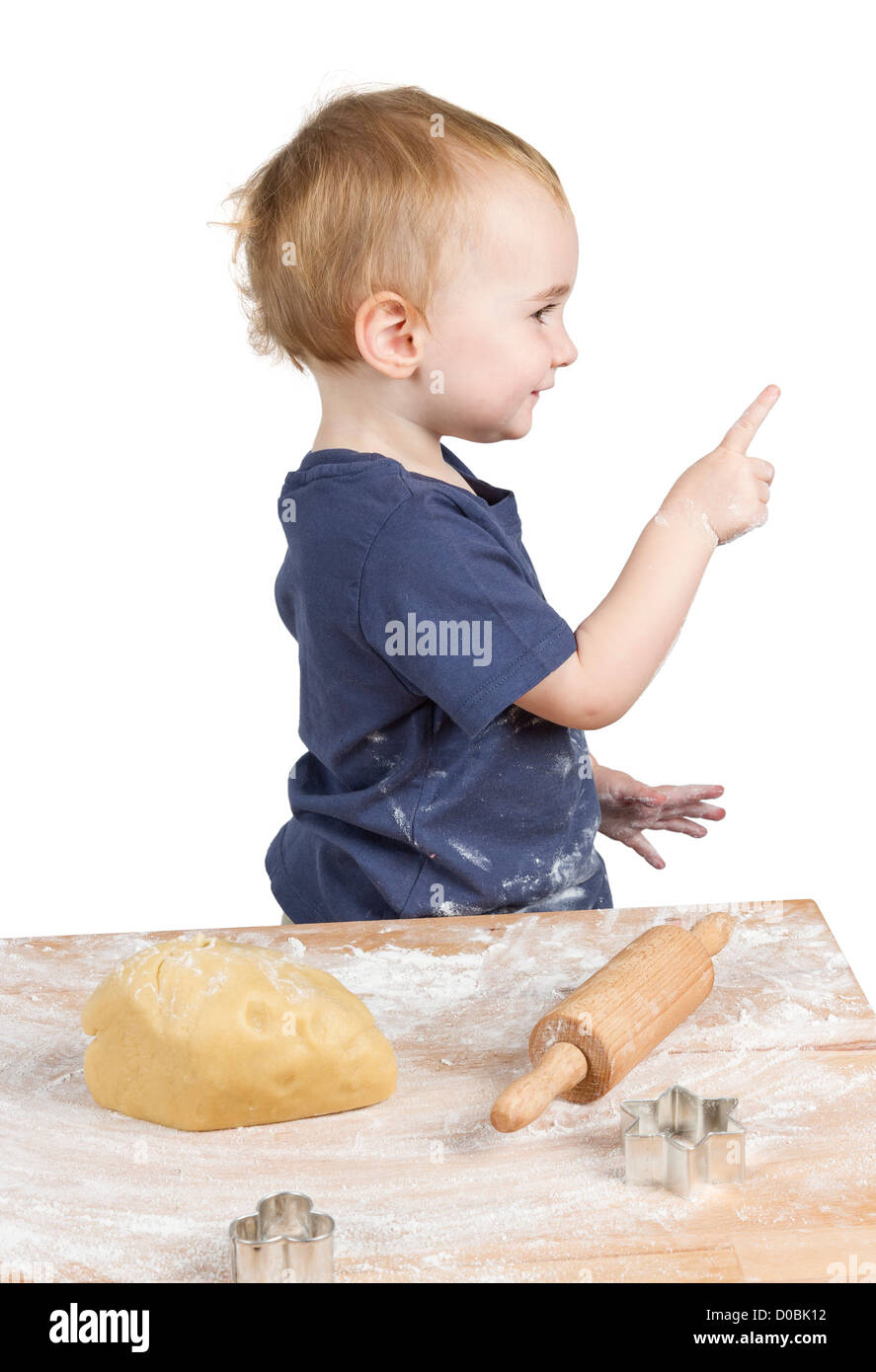 young child making cookies pointing at side - Stock Image