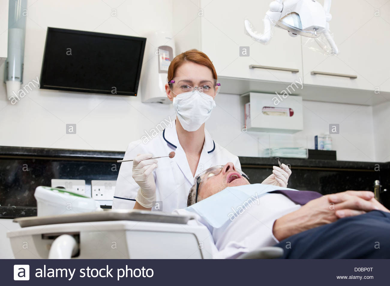 A female dentist examining a male patients teeth - Stock Image
