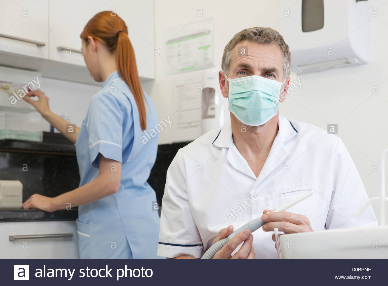 A male dentist and female dental nurse in a dental surgery - Stock Image