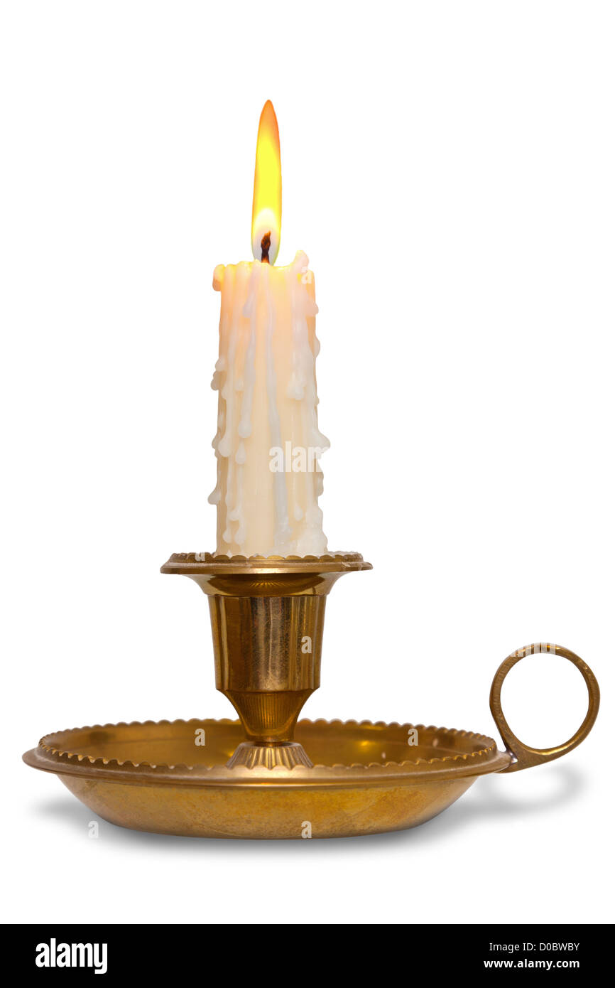 A dripping wax candle burning with flame in a traditional brass holder known as a chamberstick, isolated on a white - Stock Image