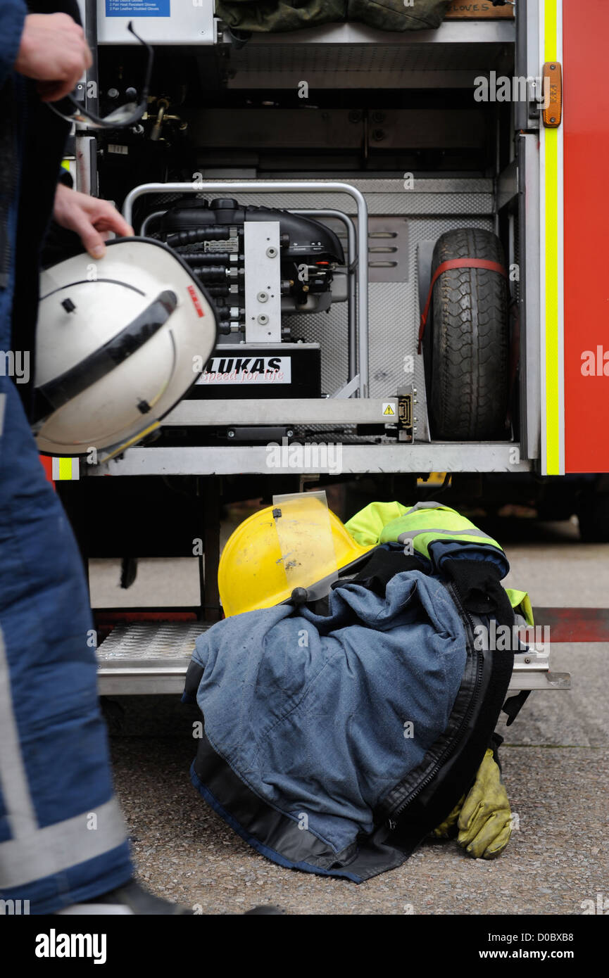 Re. Fireman of white watch at Pontypridd Fire Station in S Wales - fireman's protective helmet coat and gloves - Stock Image