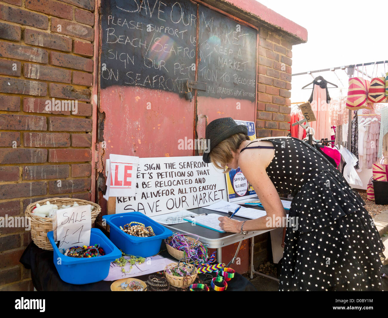 Woman signing petition to save West Pier market in Brighton & Hove - Stock Image