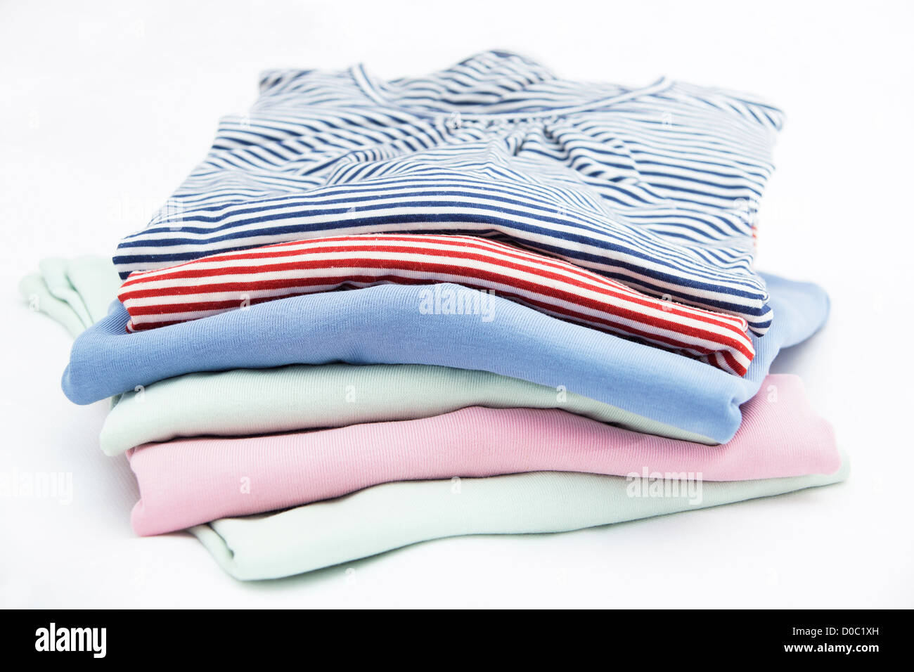 Pile of ladies jumpers / sweaters / tops isolated on a white background - Stock Image