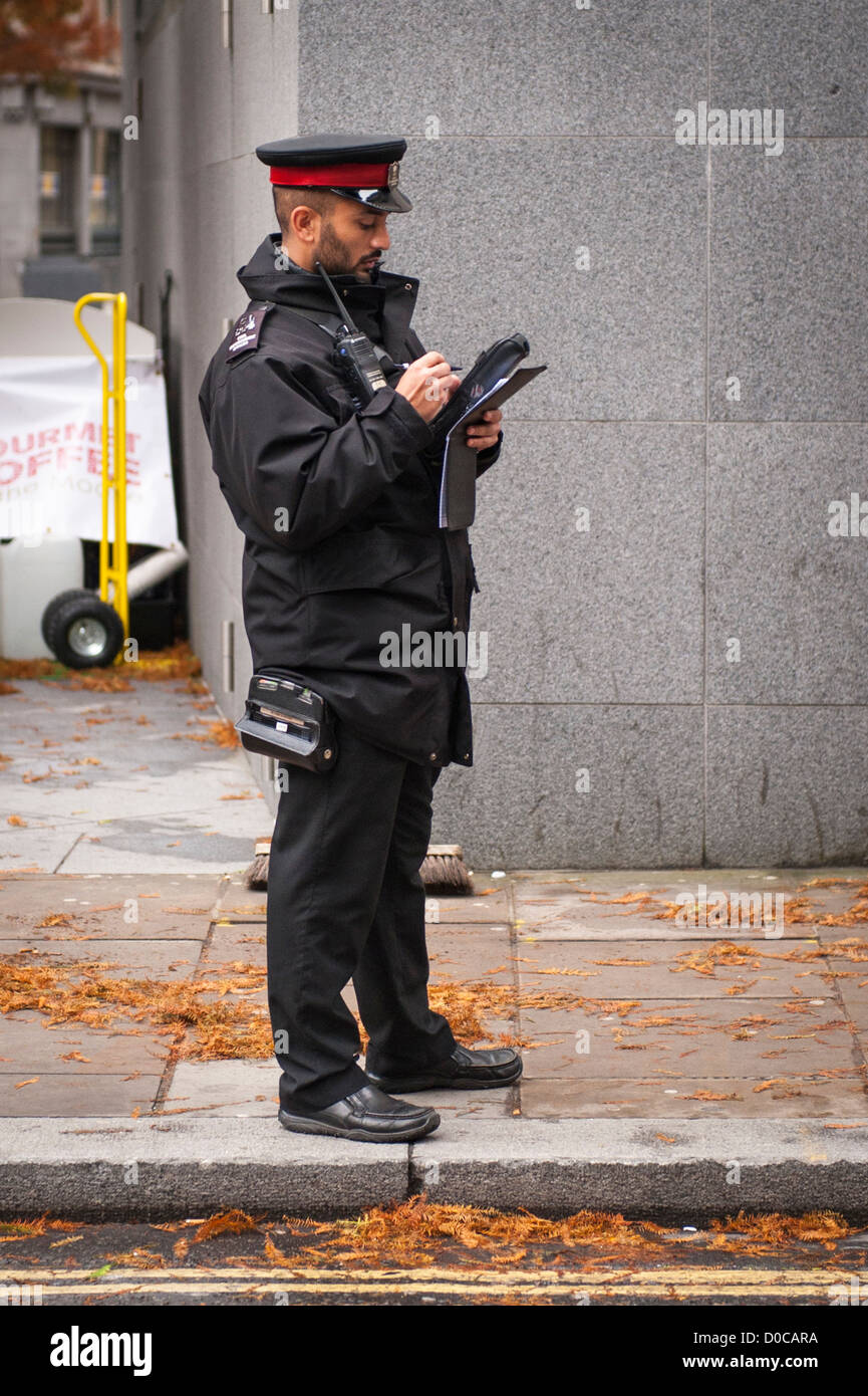 London City traffic warden uniform writing parking ticket PCN fine contravention for Iveco Stralis 450 white truck - Stock Image