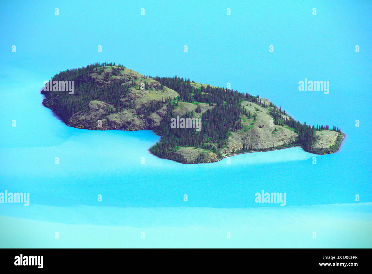 Rocky Island Amid Silt-Streaked Turquoise Waters - Stock Image
