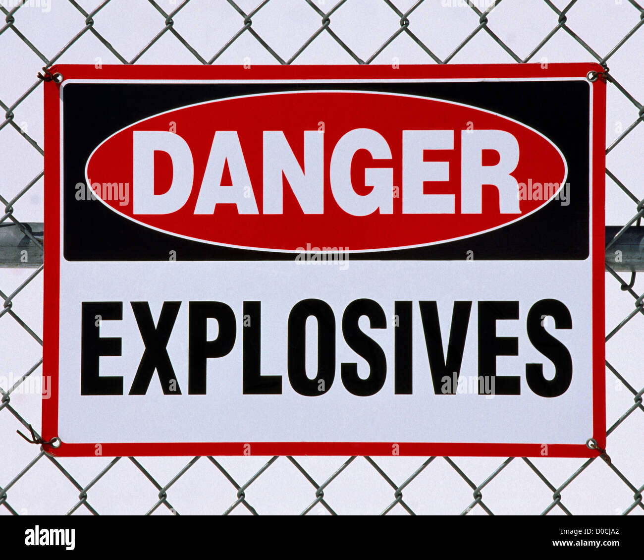 Danger Sign Indicating Explosives Lie Within the Fenced Boundary - Stock Image