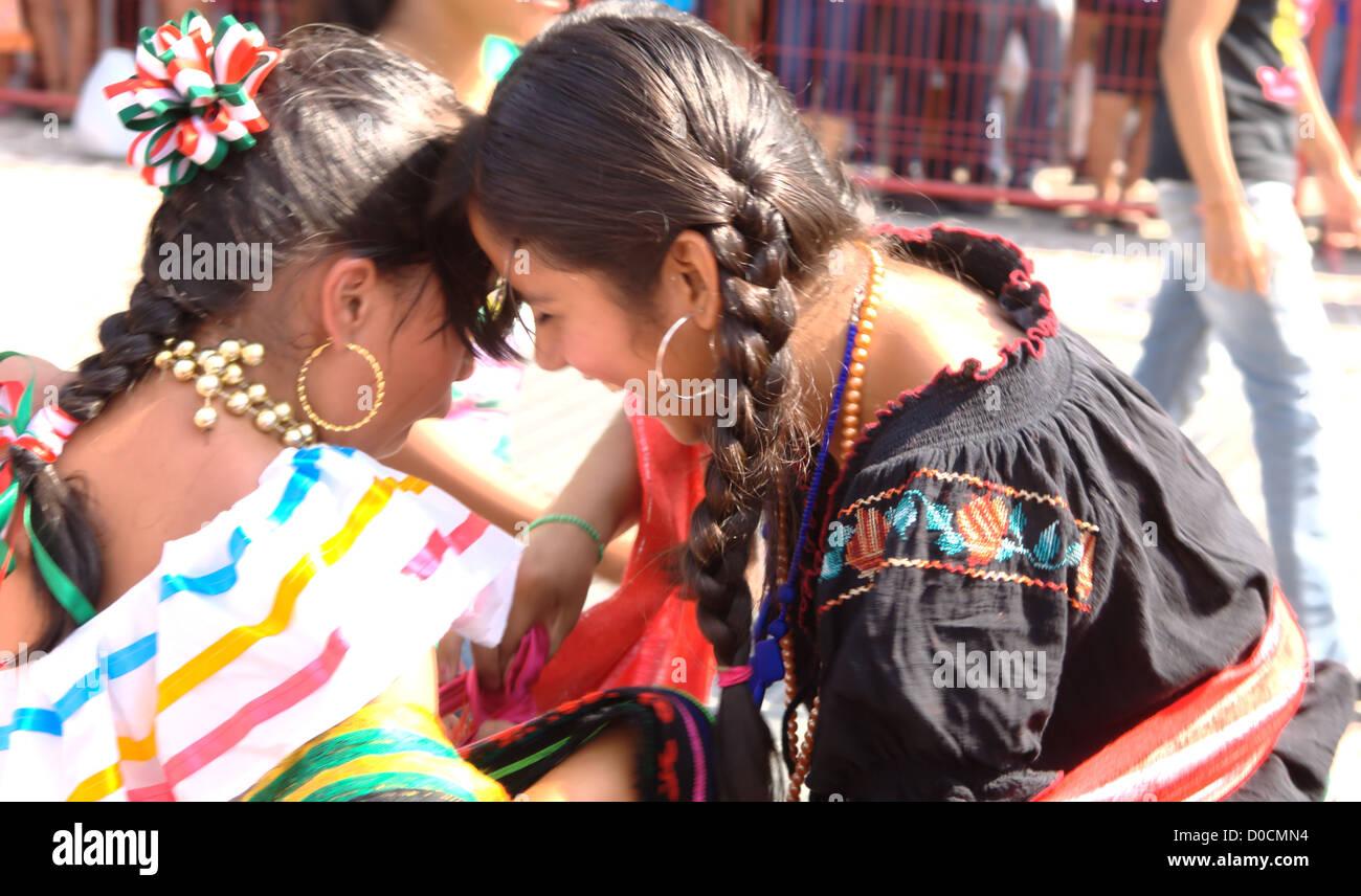 El día de la Revolución - The day of the Revolution, Mexico.Two girls have a funny moment during the El - Stock Image