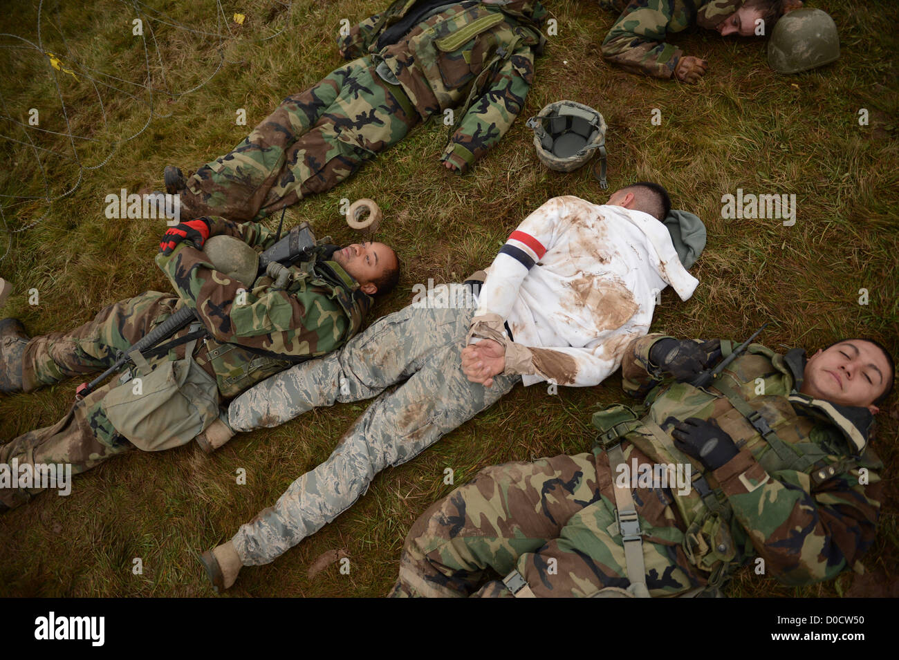 Casualties from a simulated detonated improvised explosive device lay on the ground inside the perimeter of the - Stock Image