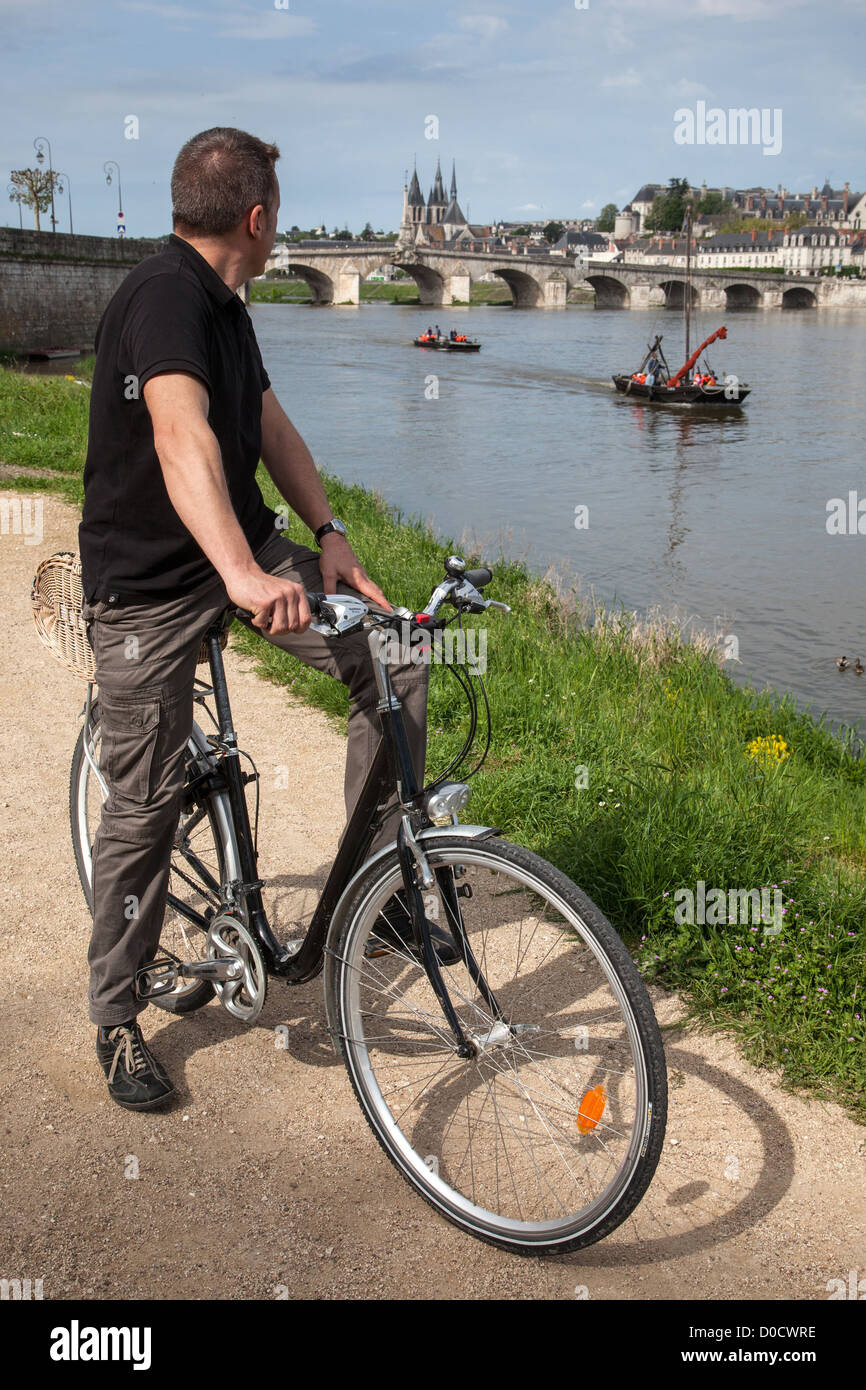 CYCLIST ON BANKS LOIRE IN FRONT WOODEN LIGHTERS CATHEDRAL SAINT-LOUIS IN BACKGROUND 'LOIRE VELO' CYCLING - Stock Image
