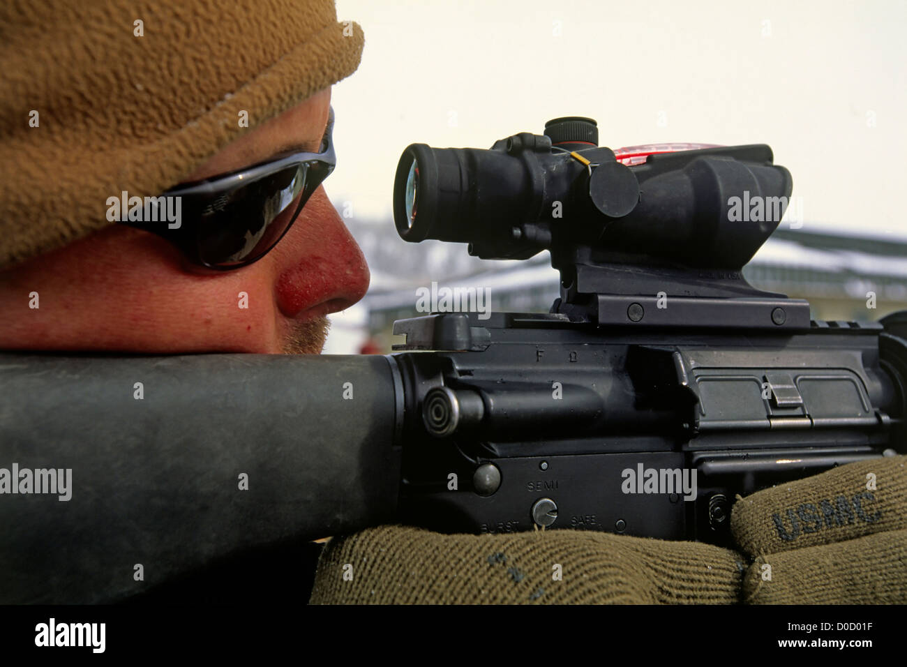 A Marine Scans the Snowy Distance Through the Scope of His M-16 During Mountain Warfare Training - Stock Image