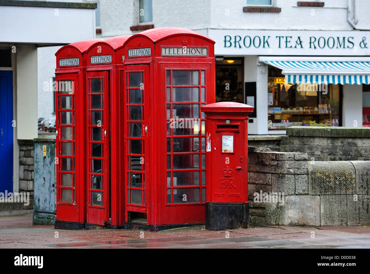 Traditional English red telephone boxes and postoffice pillar box on pavement in city street in England, UK - Stock Image