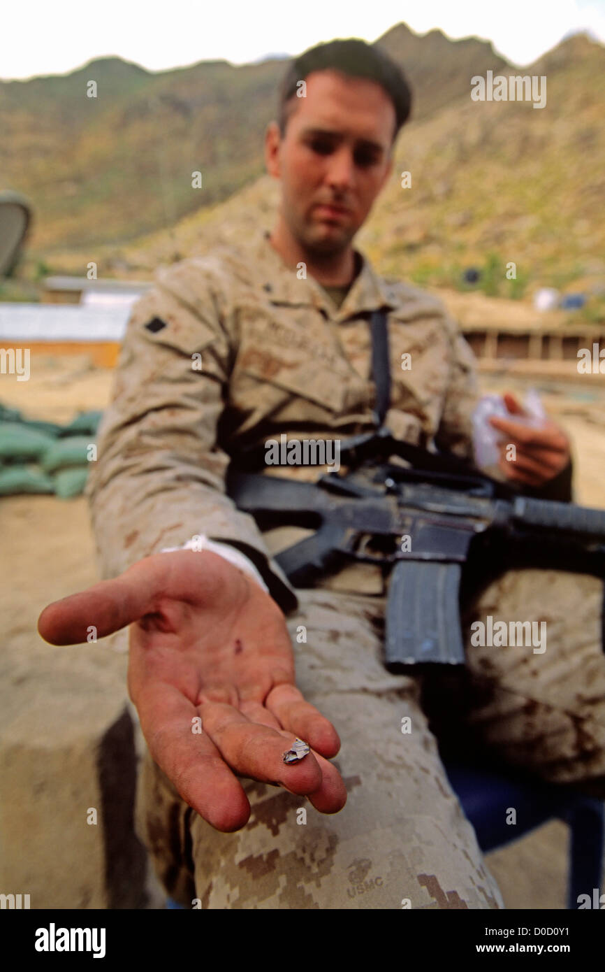 A US Marine Shows off a Piece of a Bullet Removed from His Wrist after a Firefight - Stock Image