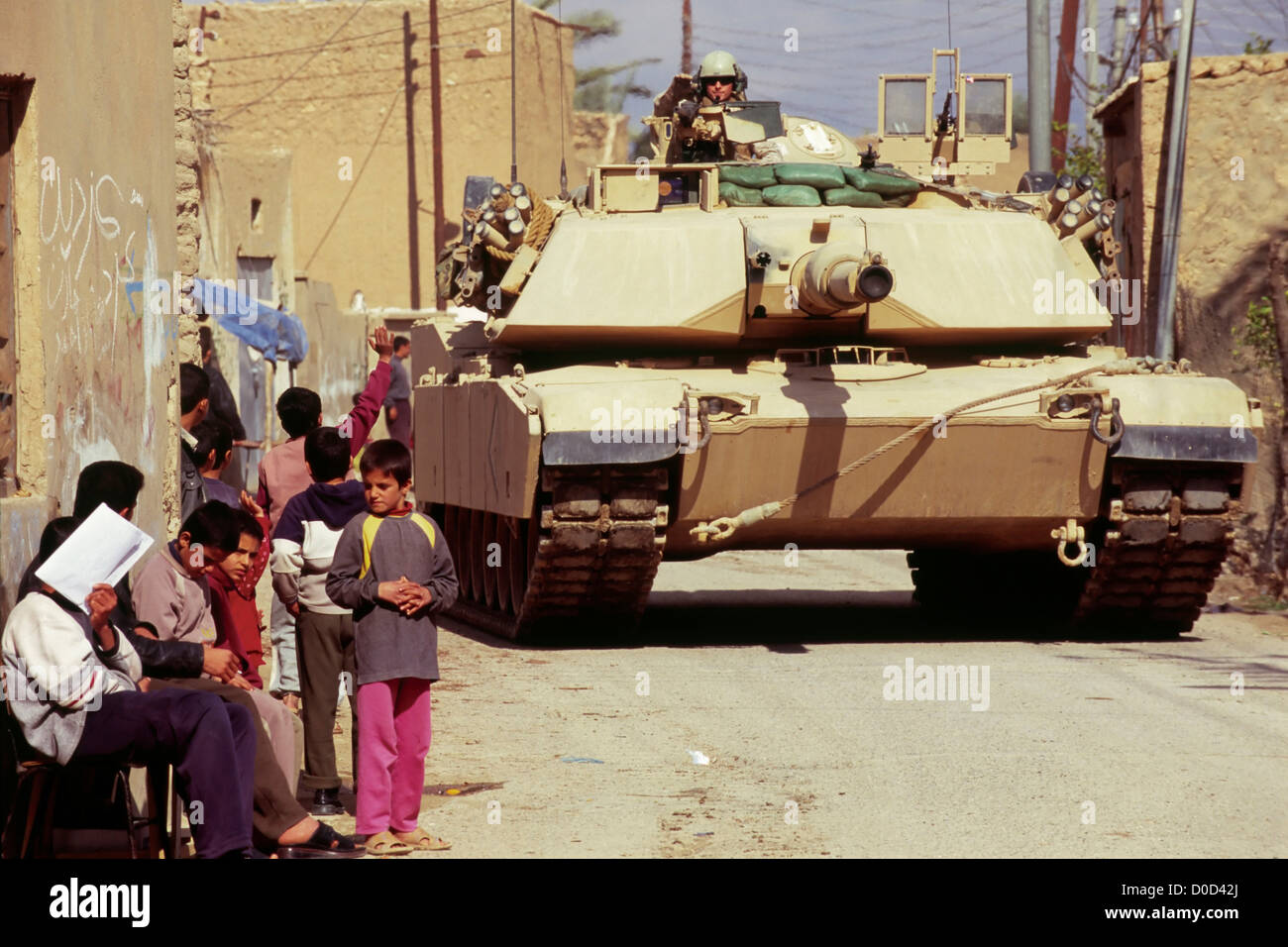 Children Gaze at a Passing Marine Corps Tank During a Combat Operation in Haqlaniyah, Iraq - Stock Image