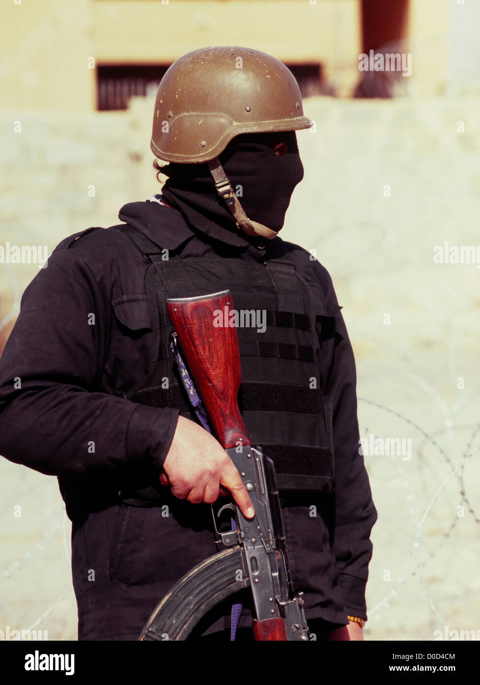 A Masked Member of the Iraqi National Police Holds His AK-47 in the City of Haditha, Iraq - Stock Image