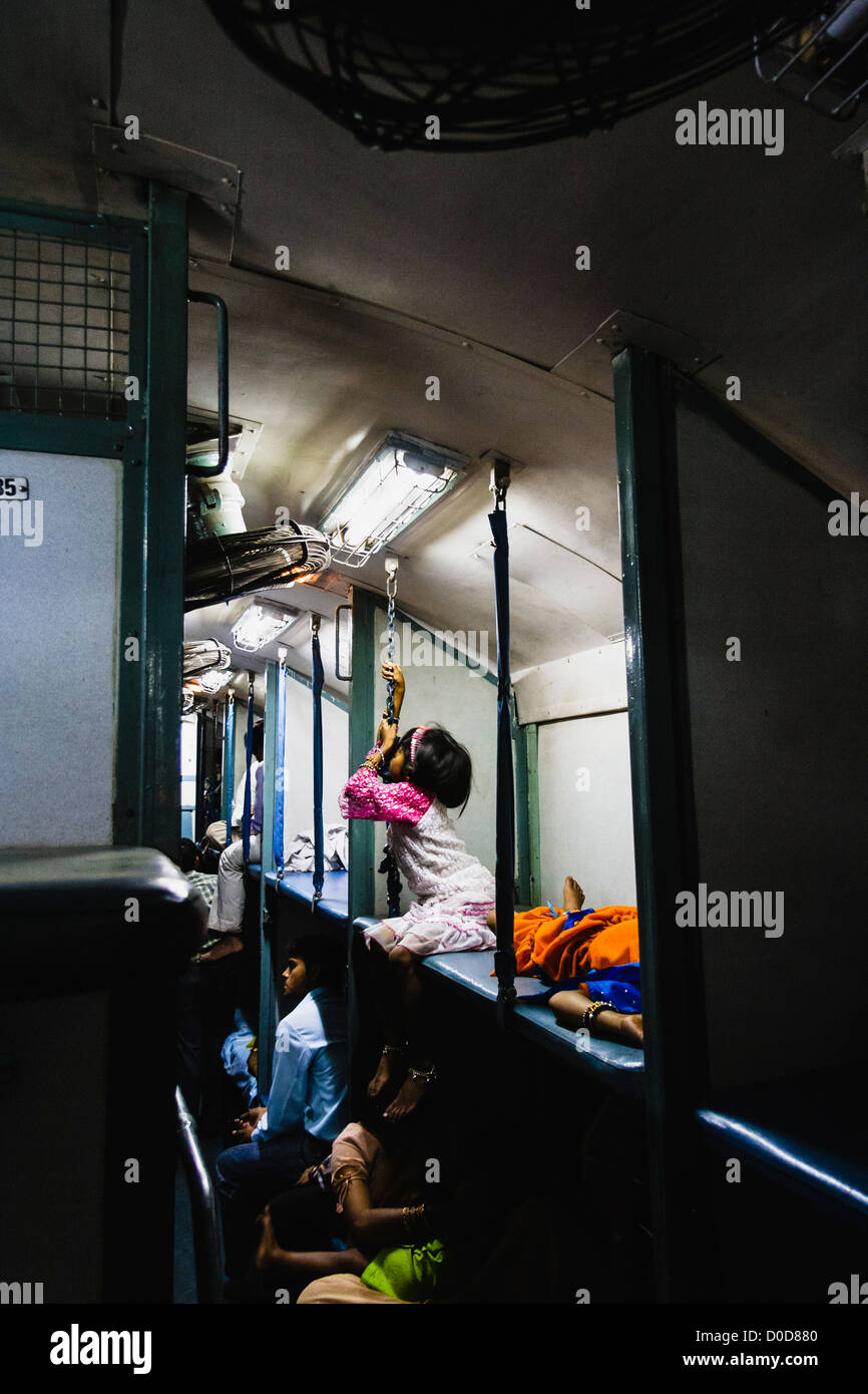 Indian girl sitting on an upper berth inside a 2nd class sleeper train. - Stock Image