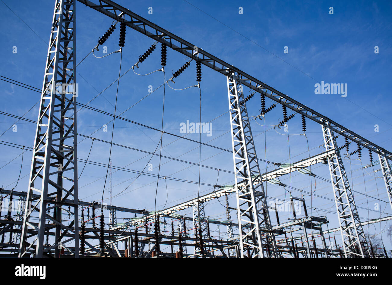 High-voltage overhead power transmission lines against blue sky - Stock Image