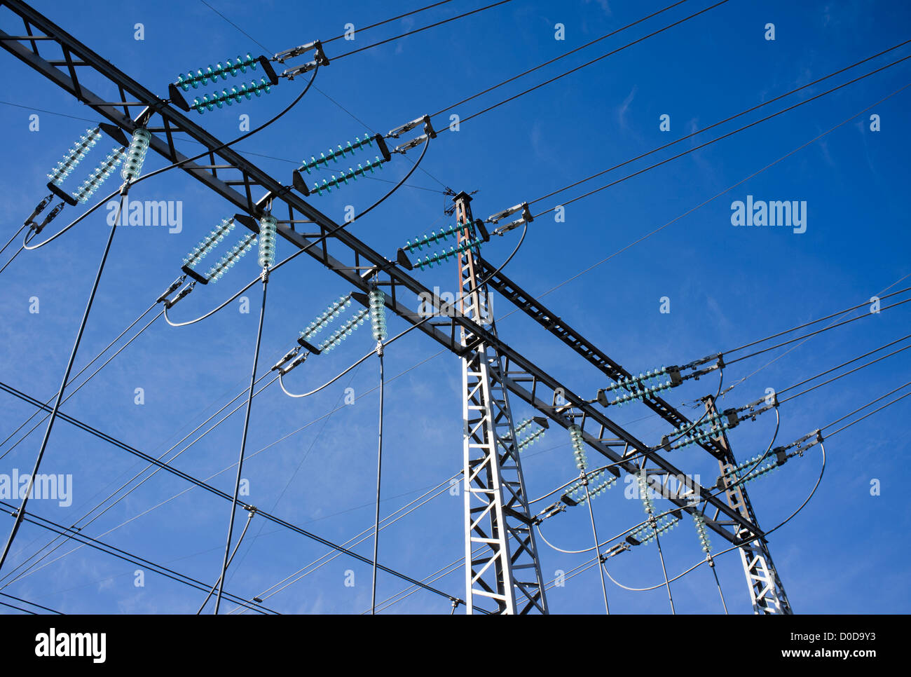 High-voltage power lines with insulators against blue sky - Stock Image