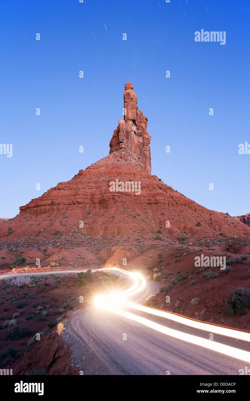 Spire and Headlights at Dawn in Valley of The Gods - Stock Image