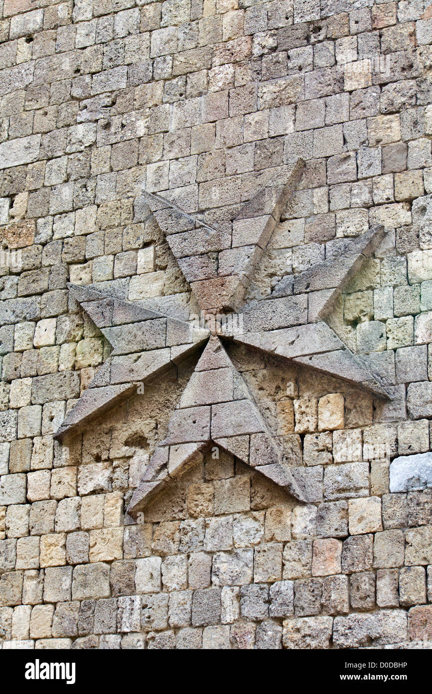 Medieval wall detail image from a castle with the maltese cross on it - Stock Image