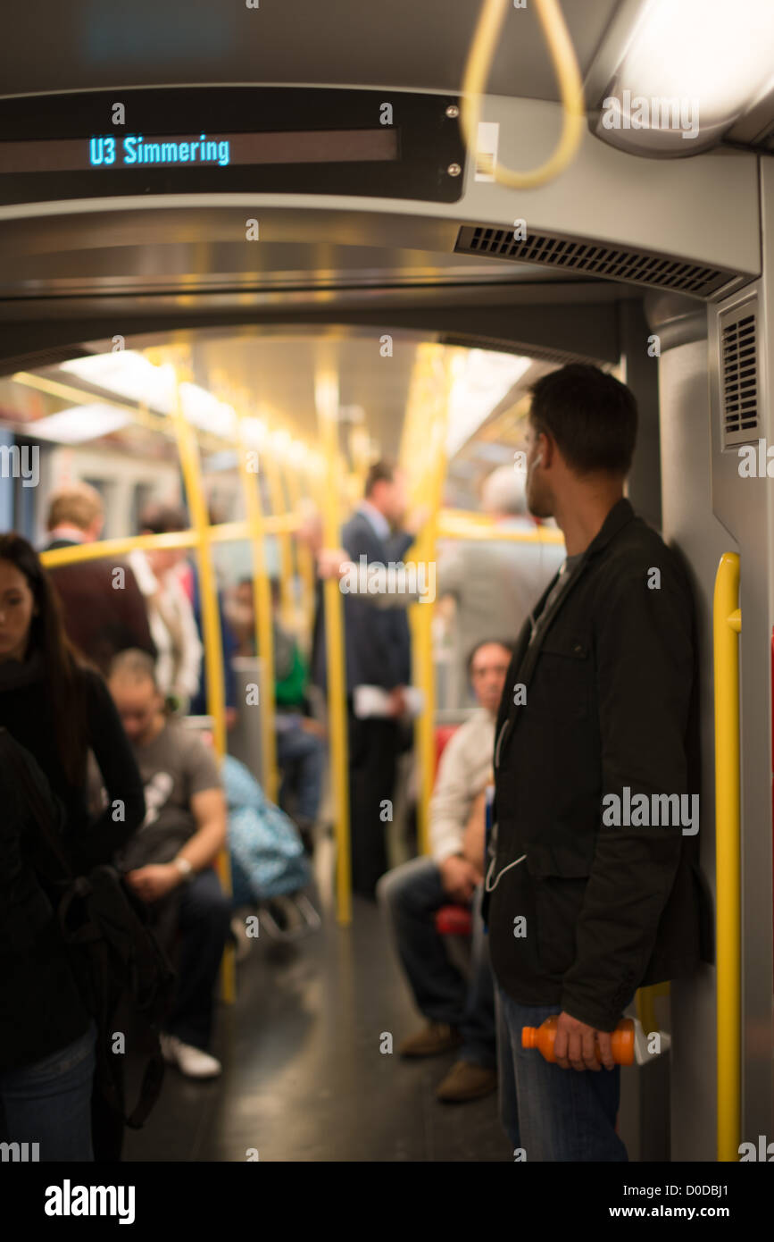 People commuting in Vienna metro U3 towards Simmering on the afternoon of October 3, 2012 in Vienna, Austria. - Stock Image