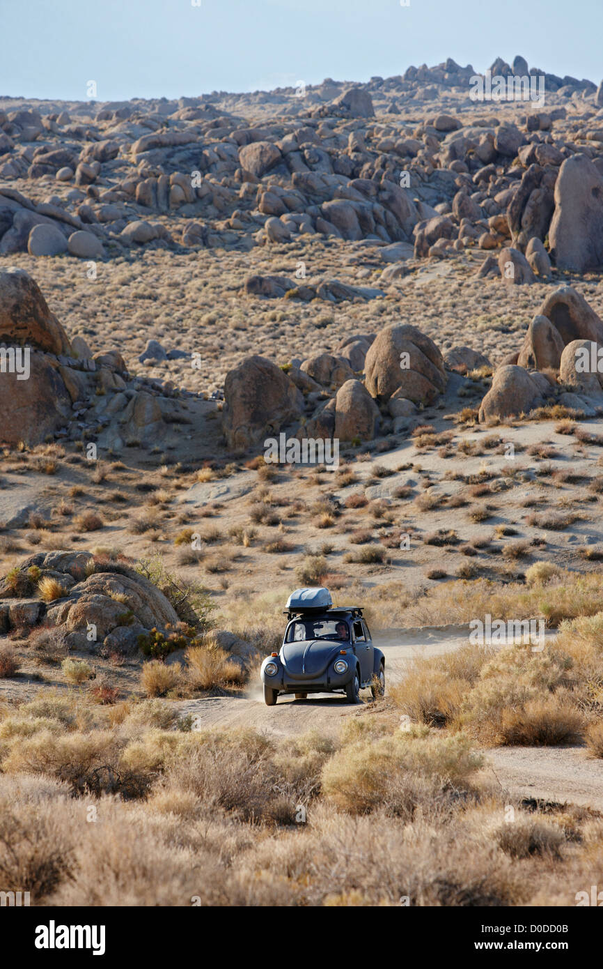 A vintage Volkswagen Beetle plies dirt road amid boulders in California's Alabama Hills below Mount Whitney - Stock Image