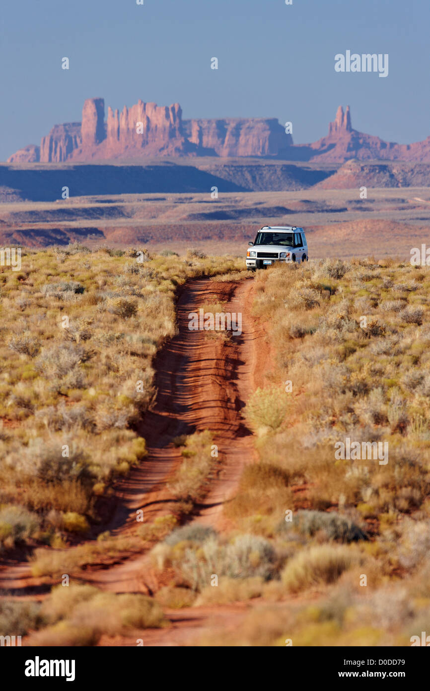A dirt road in Utah's Valley Gods Monument Valley in background 4X4 Sports Utility Vehicle on dirt road in foreground. - Stock Image
