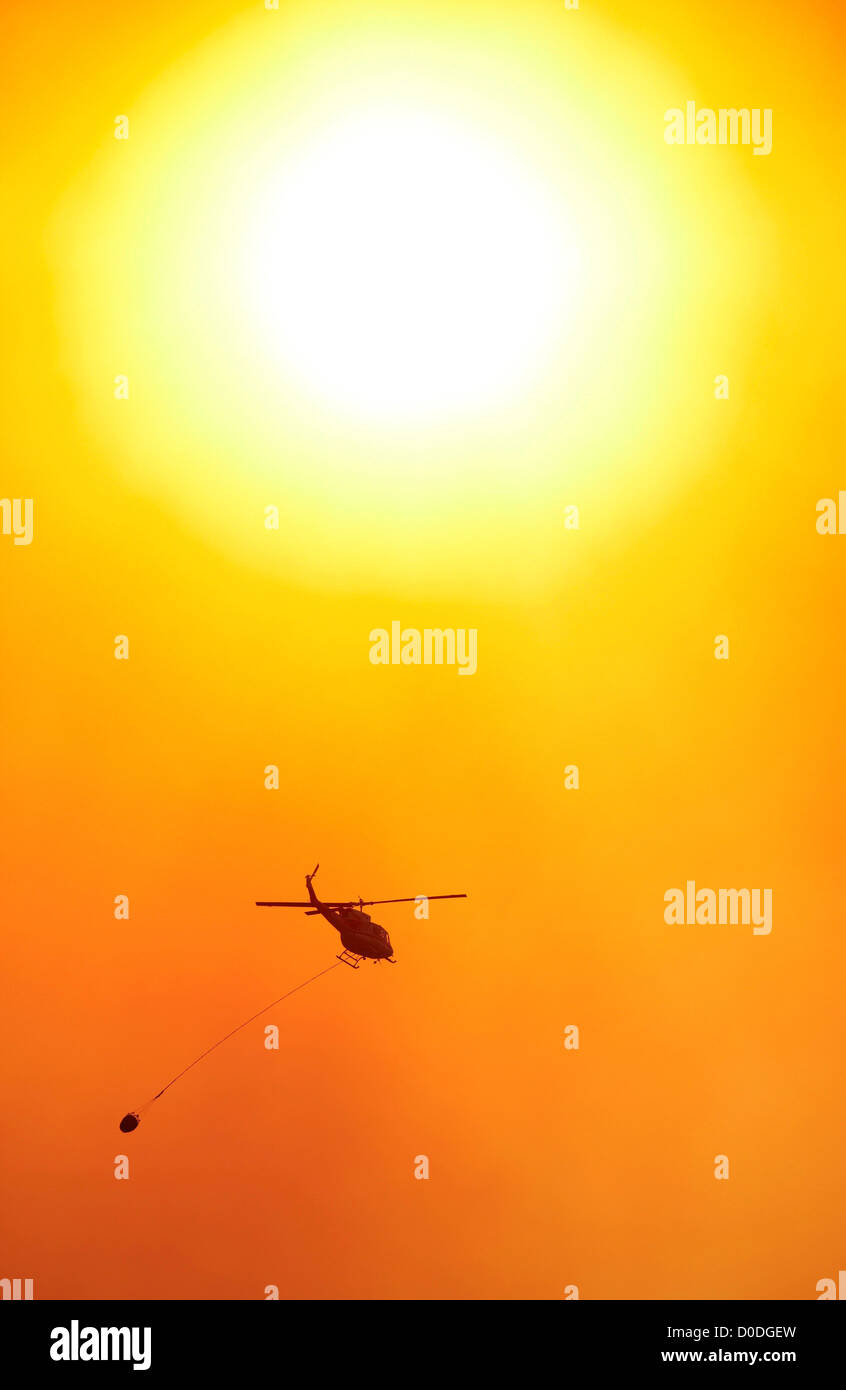 Sun silhouettes a firefighting helicopter carrying a bucket of water to a raging mountain wildfire, Colorado, USA - Stock Image