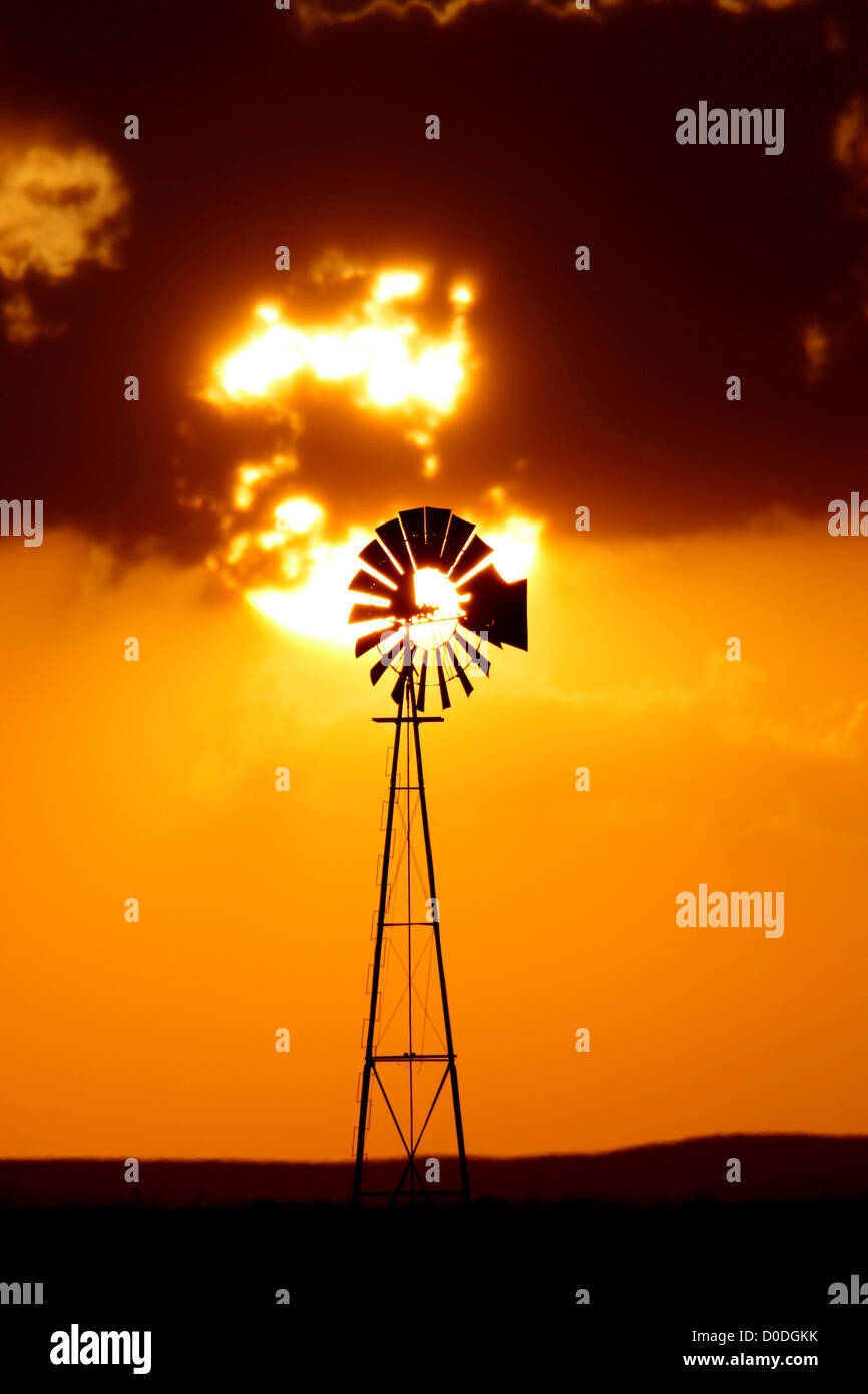 Telephoto view of setting sun and lone windmill - Stock Image