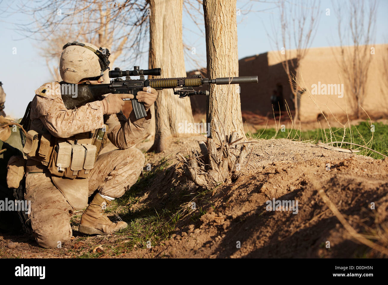 A U.S. Marine aims a Designated Marksman Rifle during a combat operation in Afghanistan's Helmand Province - Stock Image