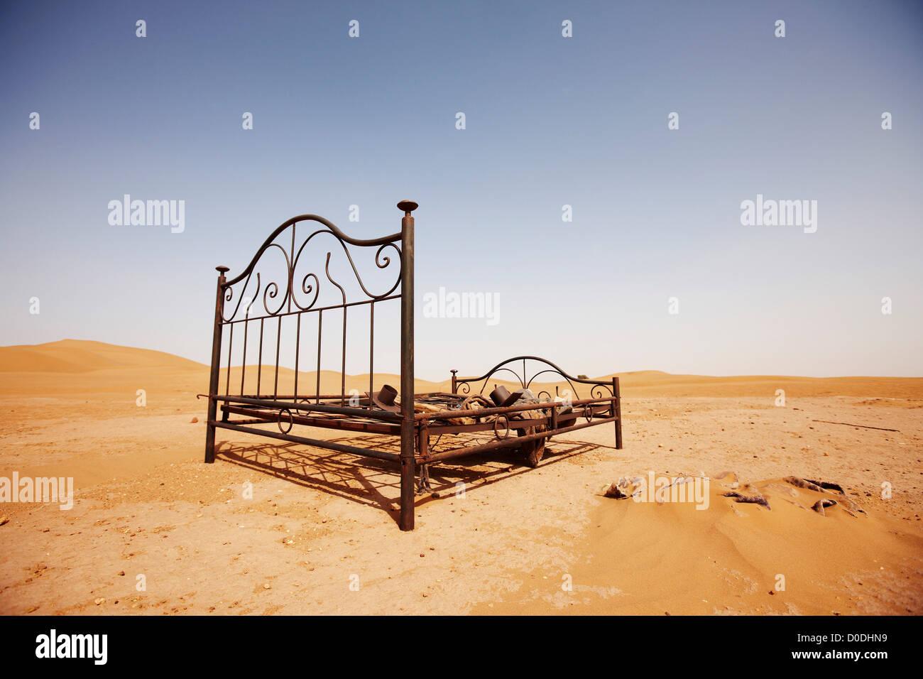 Bed frame abandoned in dunes, Erg Chegaga, interior Sahara Desert, Morocco - Stock Image