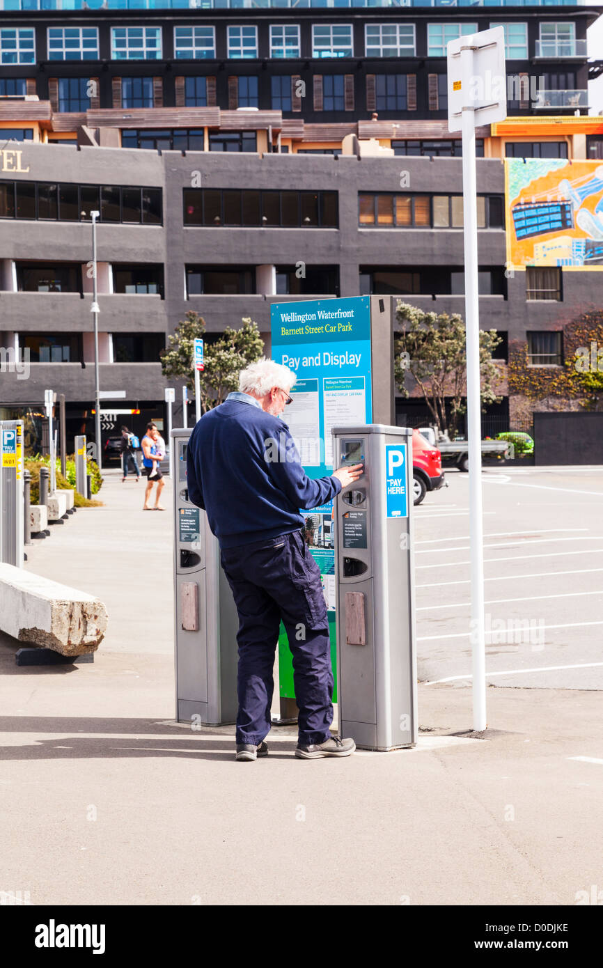 Senior man using Pay and Display parking meter in Wellington New Zealand. Model release available for senior man. - Stock Image