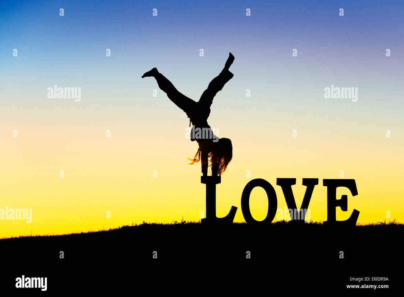 Young Girl doing a handstand on LOVE letters. Silhouette. Montage of two images for the concept of head over heels - Stock Image