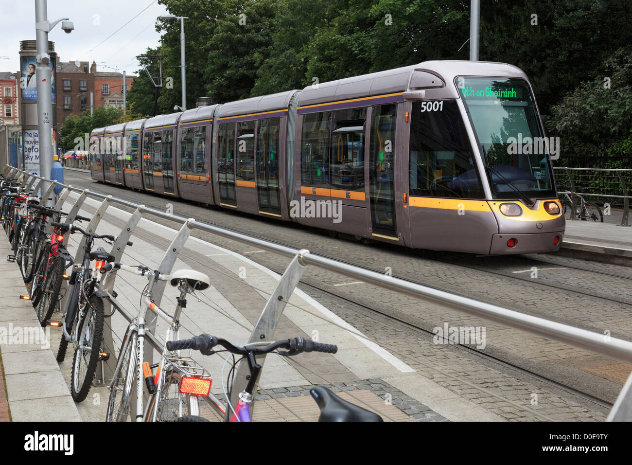 Luas Light Rail System tram in city centre station with bikes chained up to railings at Stephen's Green Dublin - Stock Image
