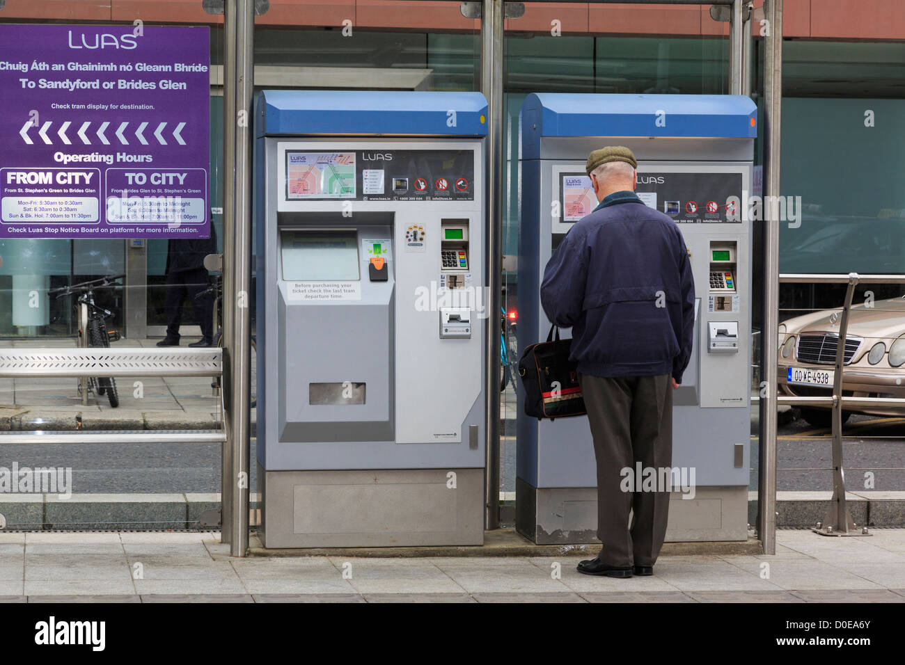 Man buying a ticket from machine on platform in Luas Light Rail System tram station in Dublin city Southern Ireland - Stock Image