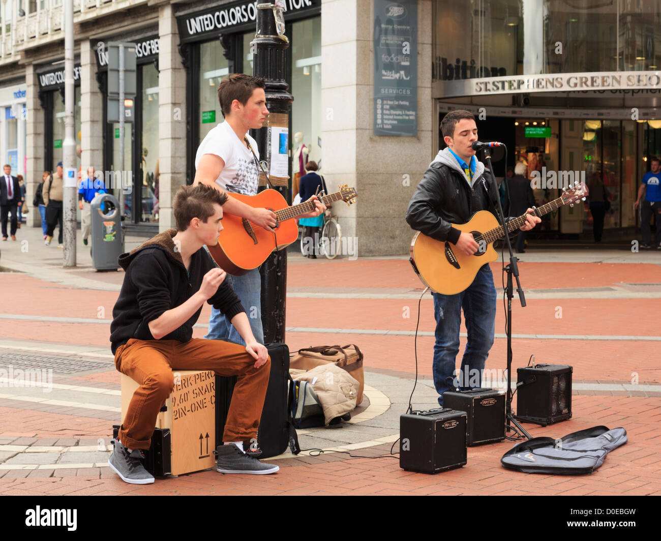Typical street scene with three Irish musicians playing guitars busking in city centre on Grafton Street Dublin - Stock Image