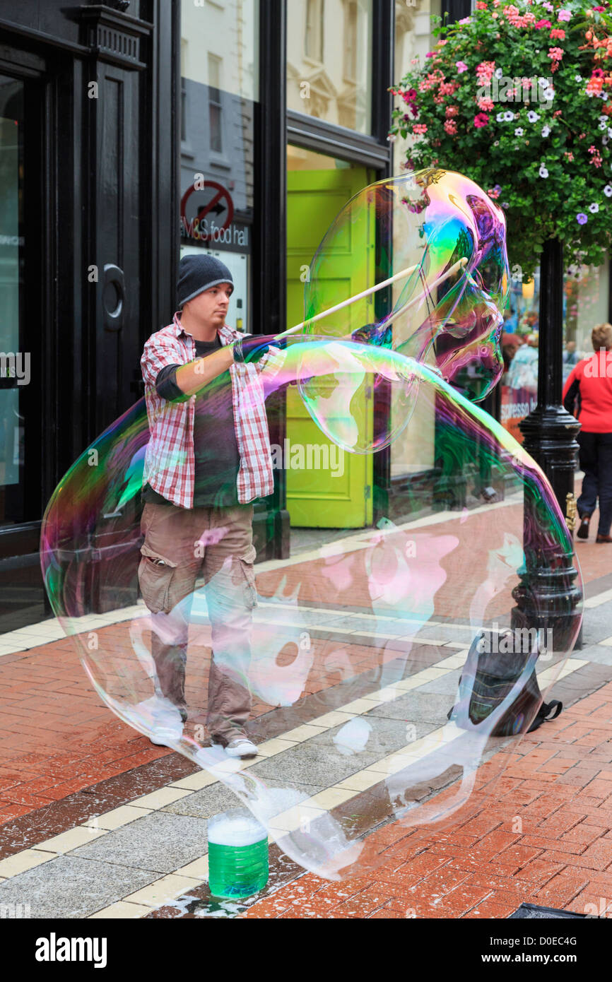Irish street entertainer making 2 large bubbles with two sticks in city centre on Grafton Street, Dublin, Southern - Stock Image