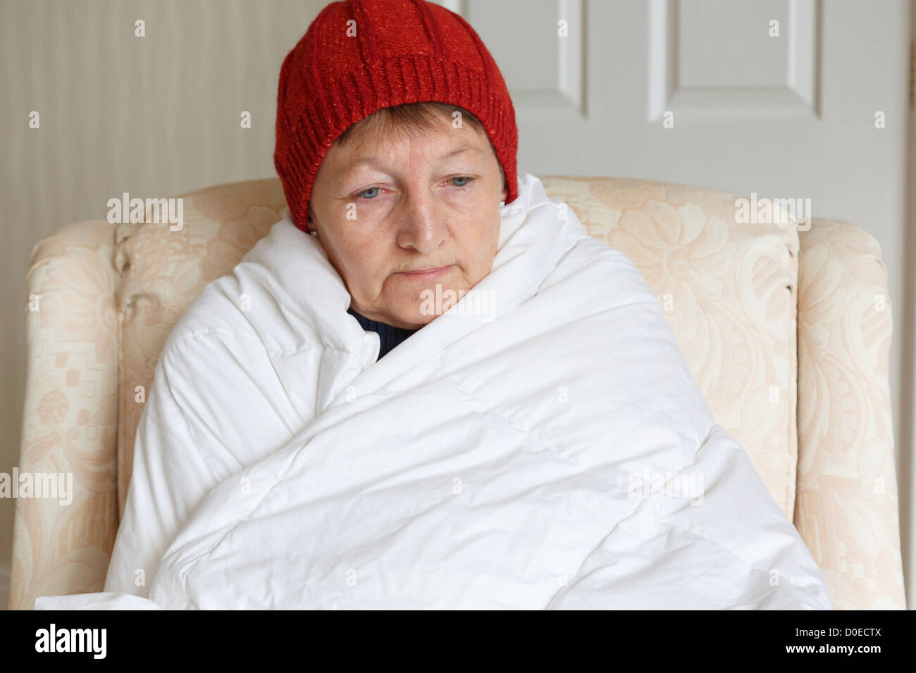 Senior woman feeling cold depressed and alone wearing a hat and wrapped in a duvet trying to keep warm and cosy - Stock Image