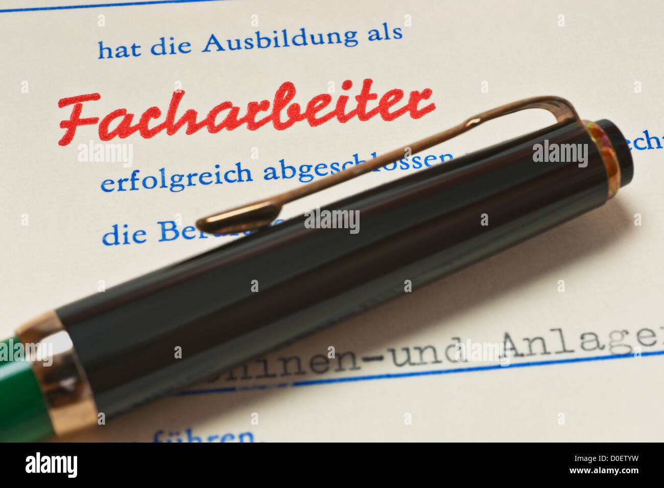 Detail photo of a craft certificate from GDR in 1989, a pen lies alongside - Stock Image