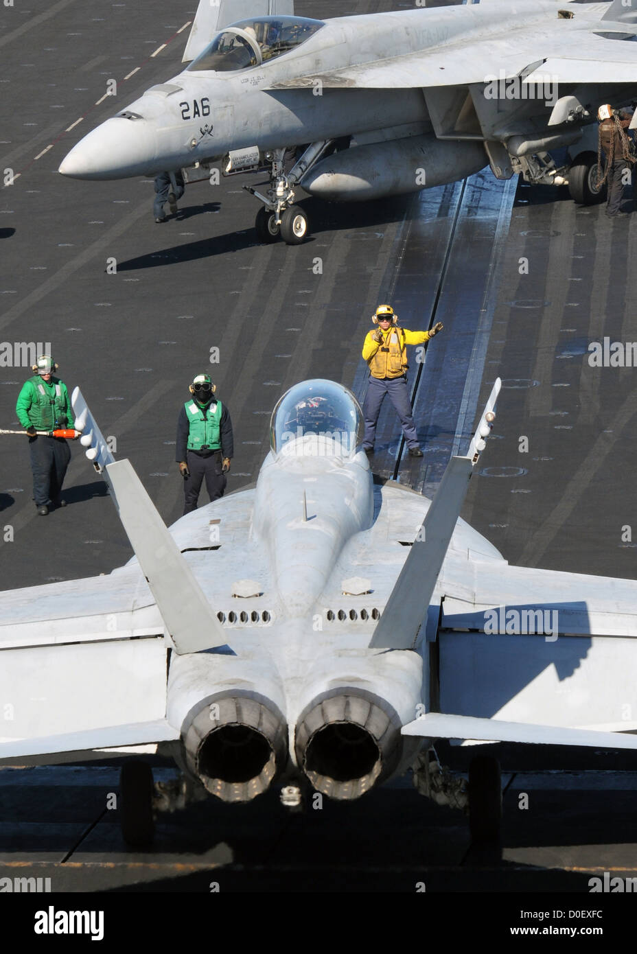 An aviation boatswain's mate directs an F/A-18C Hornet on the flight deck of the aircraft carrier USS Nimitz - Stock Image