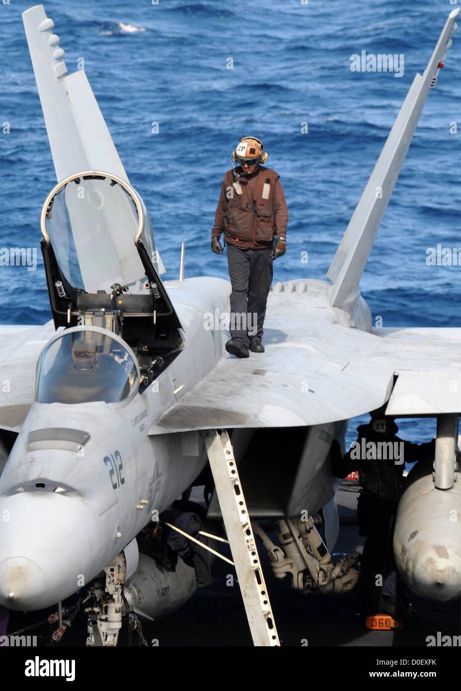 A flight deck captain does checks on an F/A-18E Super Hornet on the flight deck of the aircraft carrier USS Nimitz - Stock Image