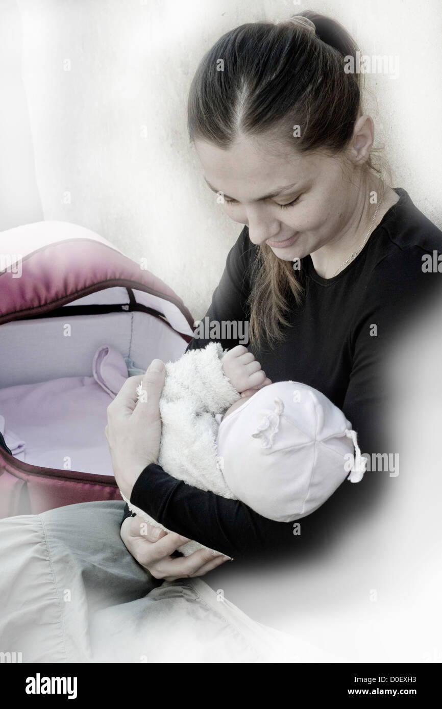 Happy Motherhood, mother cradling baby. Social photography. - Stock Image