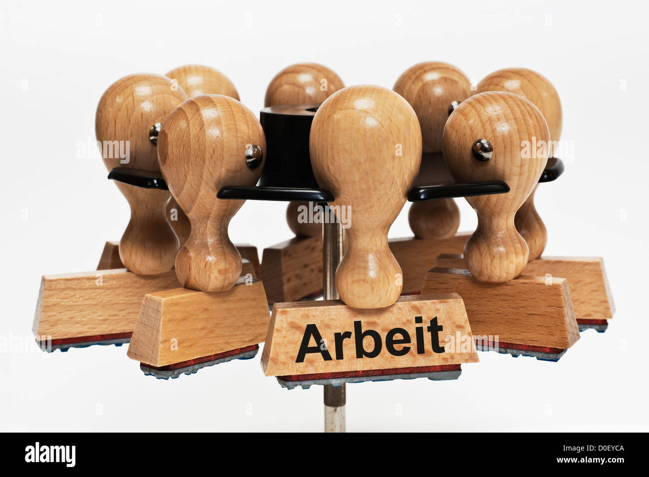 Many stamps hanging in a stamp rack, one with the German inscription Arbeit (Job), background white. - Stock Image