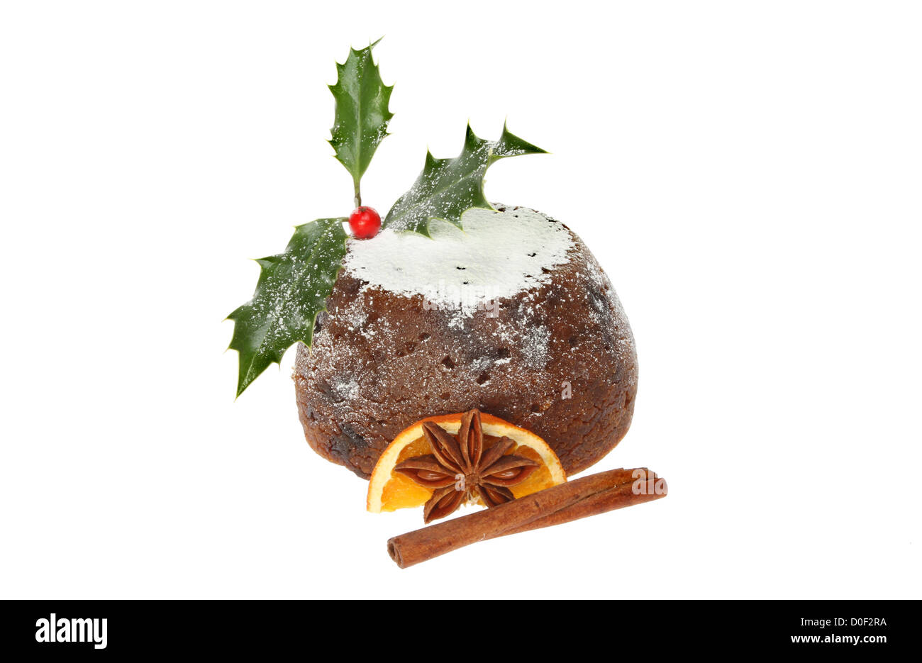 Christmas pudding decorated with holly, spice and orange isolated against white - Stock Image