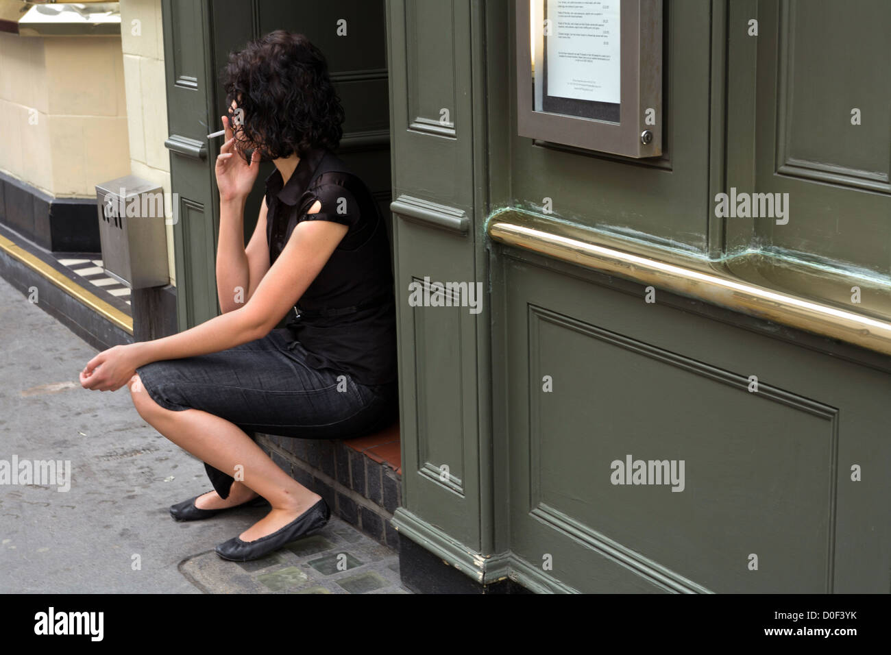A young woman has her pause for a cigarette sitting outside a pub in Covent Garden, London - Stock Image
