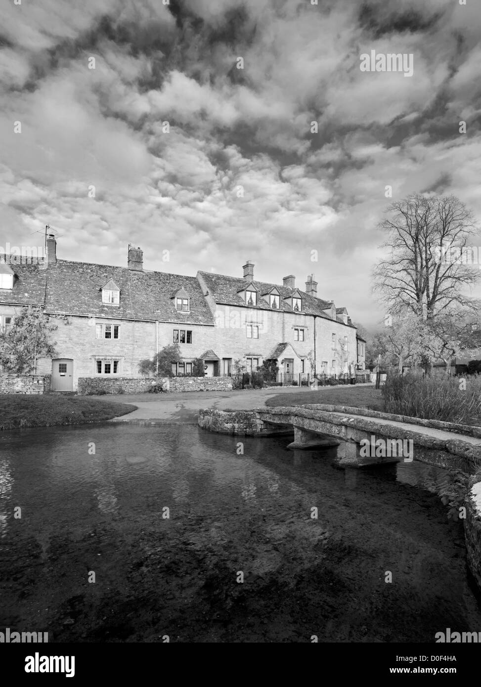 The Cotswold village of Lower Slaughter and the River Eye in black and white, Gloucestershire, England, UK - Stock Image