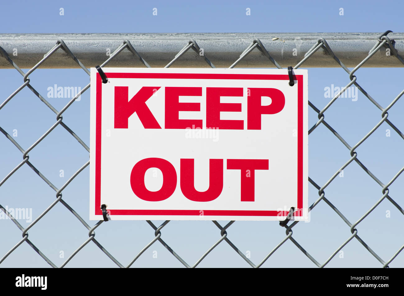 red and white keep out sign on a chain link fence - Stock Image
